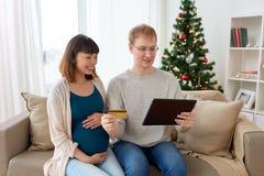 Mens en zwangere vrouw die online bij Kerstmis winkelen Stock Foto