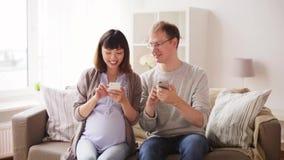 Mens en zwangere vrouw met smartphone thuis stock video