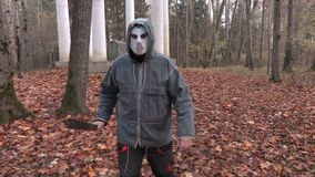 Mens in eng Halloween-masker en machete die op camera lopen stock videobeelden