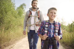 Mens expedition. Curious boy hiking with his father stock image