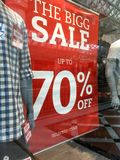 Mens fashion boutique Sale Sign. Showing markdowns up to 70% in shop front window with mannequins Royalty Free Stock Photos