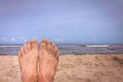 Mens feet on the beach. Close up of a feet of a man lying on the beach in summer royalty free stock photos