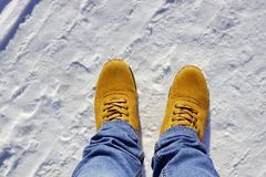 Mens feet in orange boots and jeans in the snow. Cold weather lifestyle Stock Photo
