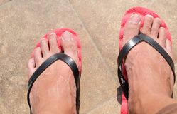 Mens feet in red flip-flops Stock Photo