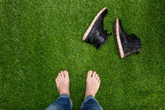 Mens feet resting on green grass with lying boots Stock Photos