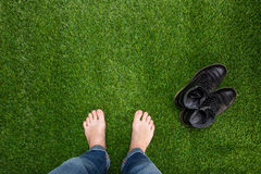 Mens feet resting on green grass Royalty Free Stock Image