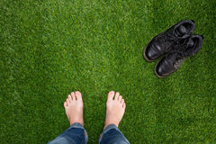 Mens feet resting on green grass with standing boots Stock Image