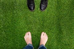Mens feet resting on green grass with standing opposite boots Royalty Free Stock Photography