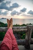 Mens feet and the sea. On the sunset background royalty free stock photo