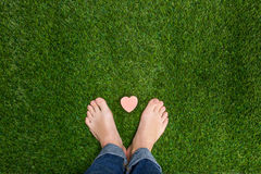 Mens feet standing on grass with small heart Royalty Free Stock Images