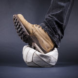 Mens foot stepped on the old leather ball Royalty Free Stock Photo