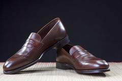 Mens Footwear Concepts. Pair of Stylish Brown Penny Loafer Shoes Placed on Straw Surface Stock Image