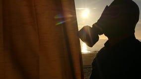 Mens in gasmasker die een gordijnclose-up sluiten stock videobeelden