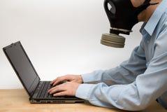 Mens in gasmasker en laptop stock fotografie