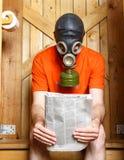 Mens in gasmaskerzitting in toilet met krant Stock Fotografie