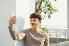 Mens geïsoleerd stading en het gebruiken van telefoon stock foto