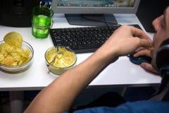 Mens gebruikend een computer en etend fastfood Stock Foto's