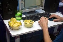 Mens gebruikend een computer en etend fastfood Stock Afbeeldingen