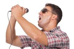 Mens gebruikend hoofdtelefoons en zingend aan de microfoon Stock Foto's