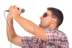 Mens gebruikend hoofdtelefoons en zingend aan de microfoon Stock Afbeelding