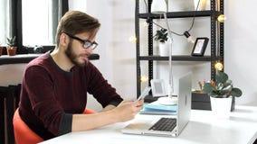 Mens gebruikend smartphone en babbelend, rust in bureau stock videobeelden