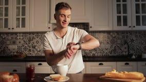 Mens Gebruikend Smartwatch en Drinkend Koffie stock videobeelden