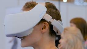Mens gebruikend virtuele werkelijkheidshoofdtelefoon en rond bekijkend VR-tentoonstelling stock video