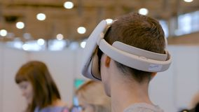 Mens gebruikend virtuele werkelijkheidshoofdtelefoon en rond bekijkend VR-tentoonstelling stock footage