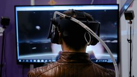 Mens gebruikend virtuele werkelijkheidshoofdtelefoon en spelend het spel van de actieschutter stock videobeelden