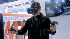 Mens gebruikend virtuele werkelijkheidshoofdtelefoon en trekkend met speciale bedieningshendel stock videobeelden