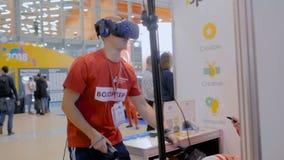 Mens gebruikend VR-hoofdtelefoon en spelend actief sportspel met speciale bedieningshendel stock videobeelden