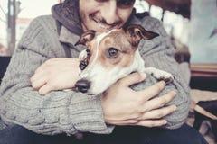 Mens geknuffel met zijn hond in de winter royalty-vrije stock foto's