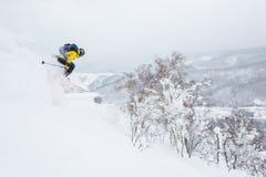 Mens in gele sprongen van een kroonlijst dichtbij de top van een kleine piek in backcountry van Hokkaido, Japan stock foto's
