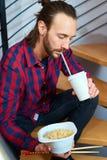 Mens in geruite overhemdszitting op treden en het eten van Aziatisch voedsel Stock Afbeeldingen