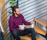 Mens in geruite overhemdszitting op treden en het eten van Aziatisch voedsel Stock Foto's