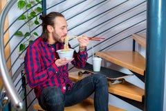 Mens in geruite overhemdszitting op treden en het eten van Aziatisch voedsel Royalty-vrije Stock Foto's