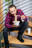 Mens in geruite overhemdszitting op treden en het eten van Aziatisch voedsel Royalty-vrije Stock Foto