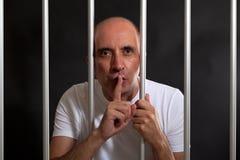 Mens in gevangenis het gesturing om stilte te houden stock foto