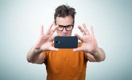 Mens in glazen door smartphone worden gefotografeerd die Stock Afbeeldingen