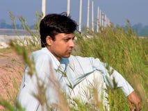 Mens in gras naast strand Stock Foto