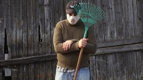 Mens in Halloween-masker met hark bij de oude schuur stock videobeelden