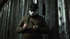 Mens in Halloween-masker scherpend mes op mes stock video