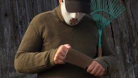 Mens in Halloween-maskercontrole de bladscherpte stock videobeelden