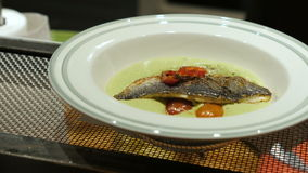 Mens hand in latex gloves put down cooked fish in the plate with vegetables and white sauce. cook stock video