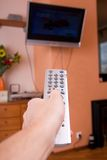 Mens hand with remote control. Mens hand with a remote control Stock Photo