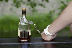Mens in handcuffs die met een fles onderling wordt verbonden Royalty-vrije Stock Afbeelding