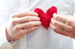 Mens hands hold a toy heart Stock Image
