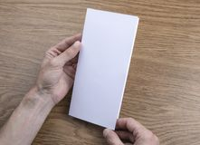 Mens hands holding white booklet stock photography