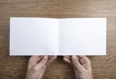 Mens hands holding white booklet royalty free stock image
