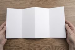Mens hands holding white booklet. Mens hands holding empty white booklet on wooden background. View from above stock image